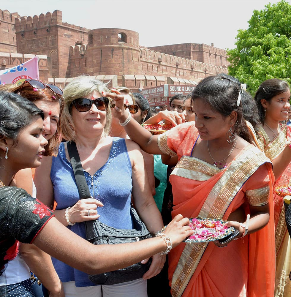 Tourists being welcomed by girls on the occasion of World Heritage Day in Agra.