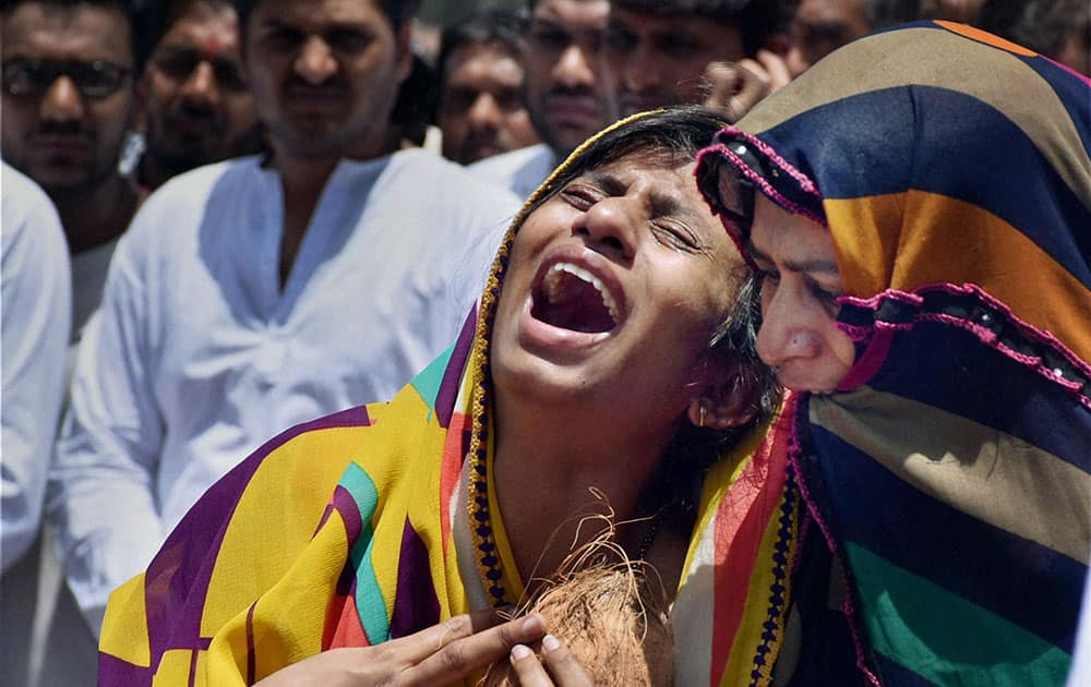 The wife of Bhavin Khunt mourns his death during his funeral procession in Surat.