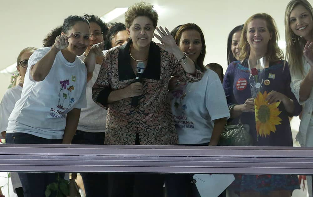 Brazil's President Dilma Rousseff, second left, looks out from at the Planalto Presidential Palace window during the