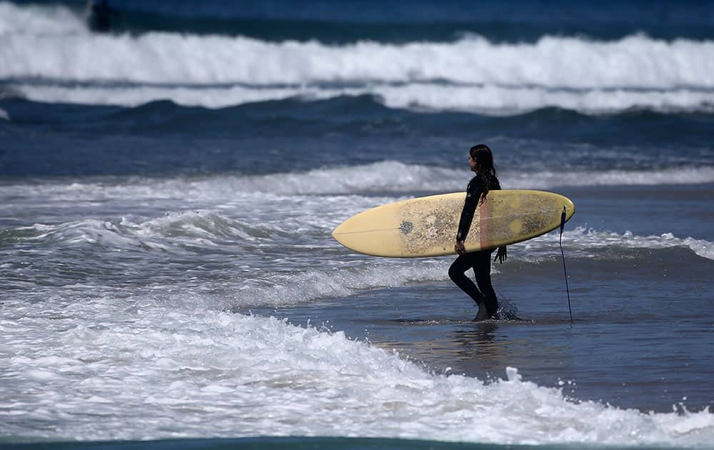 A surfer strolls into the waves a Cardiff State Beach where warm temperatures prevail in Encinitas, Calif.