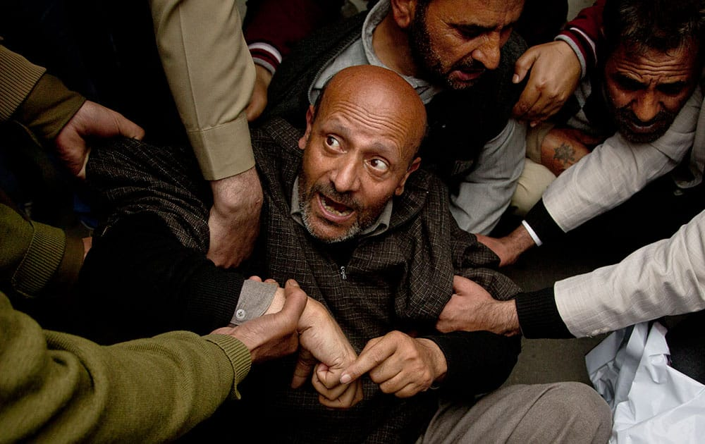 policemen detain Engineer Rashid Ahmed, an independent member of the Jammu and Kashmir state assembly and head of Awami Itihaad party (AIP), during a protest in Srinagar, India.
