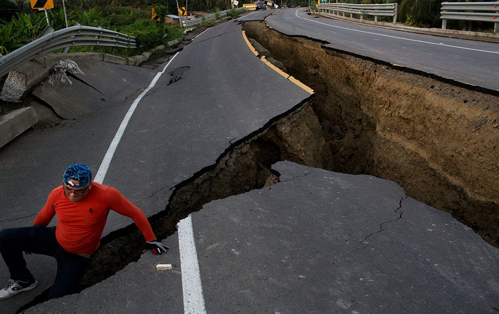 A man jokes around after taking some pictures of a section of highway that collapsed due to a 7.8-magnitude earthquake, in Chacras, Ecuador.