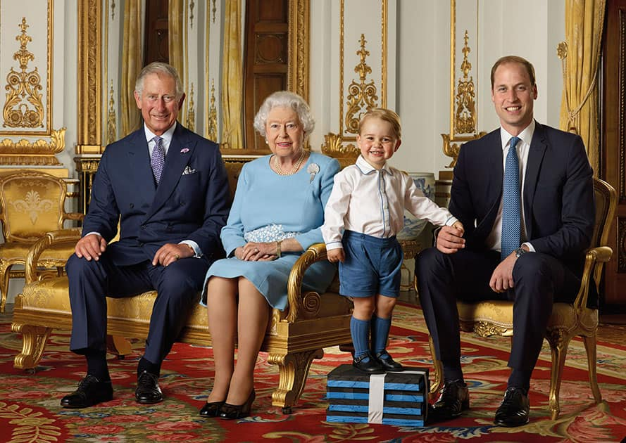 This image released by the Royal Mail, Britain's Prince George stands on foam blocks during a photo shoot for the Royal Mail in the summer of 2015 in the White Drawing Room at Buckingham Palace in London for a stamp sheet to mark the 90th birthday of Britain's Queen Elizabeth II. The image features four generations of the Royal family, from left, Prince Charles, Queen Elizabeth II, Prince George and Prince William, the Duke of Cambridge.