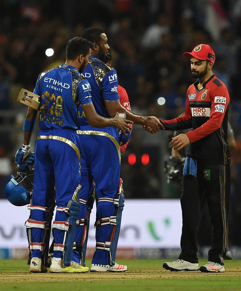 Mumbai Indians players Hardik Pandya and Kieron Pollard being greeted by Rohit Sharma of Royal Challengers Bangalore after the victory during the IPL match in Mumbai.