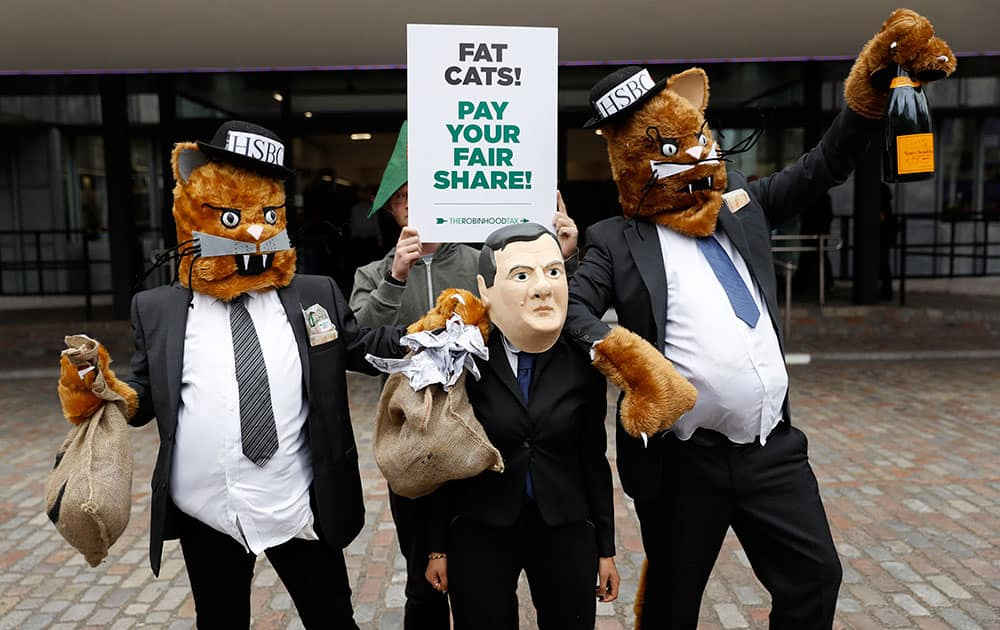 Robin Hood Tax campaigners pose for photographers dressed as fat cats and Britain's Chancellor of the Exchequer George Osborne outside the HSBC annual general meeting at the Queen Elizabeth II conference centre in London.