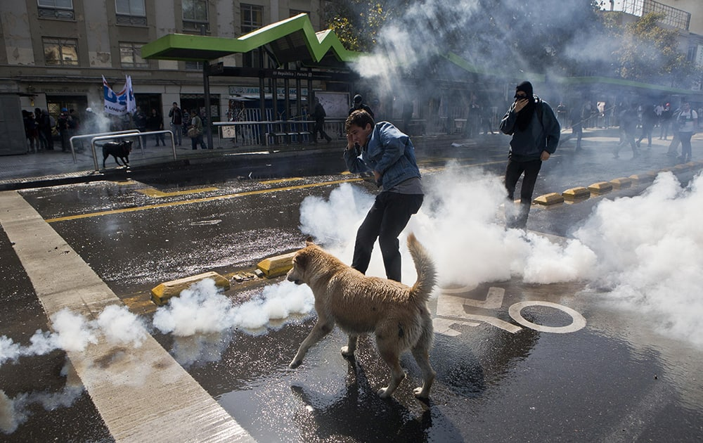 A student kicks a tear gas canister during a protest demanding that the government make true its promise of free education, in Santiago, Chile.