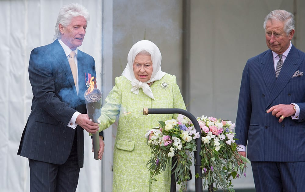 Britain's Queen Elizabeth II is handed a torch by Bruno Peek, Originator & Pageantmaster, with which to light the principal beacon to celebrate her 90th birthday, watched by her eldest son, Prince Charles.