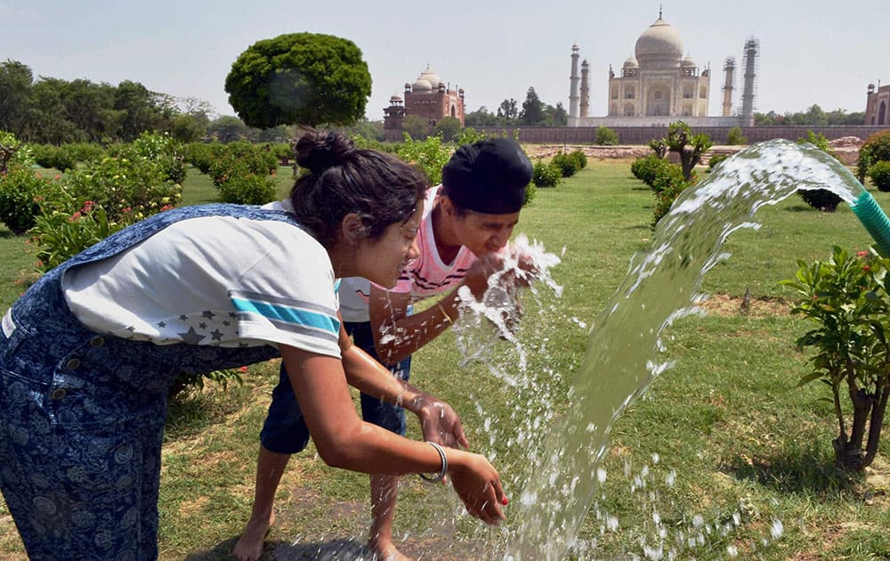 Tourists splash water on their faces to get relief from heat at Mehtab Bagh behind Taj Mahal during a hot summer day in Agra.