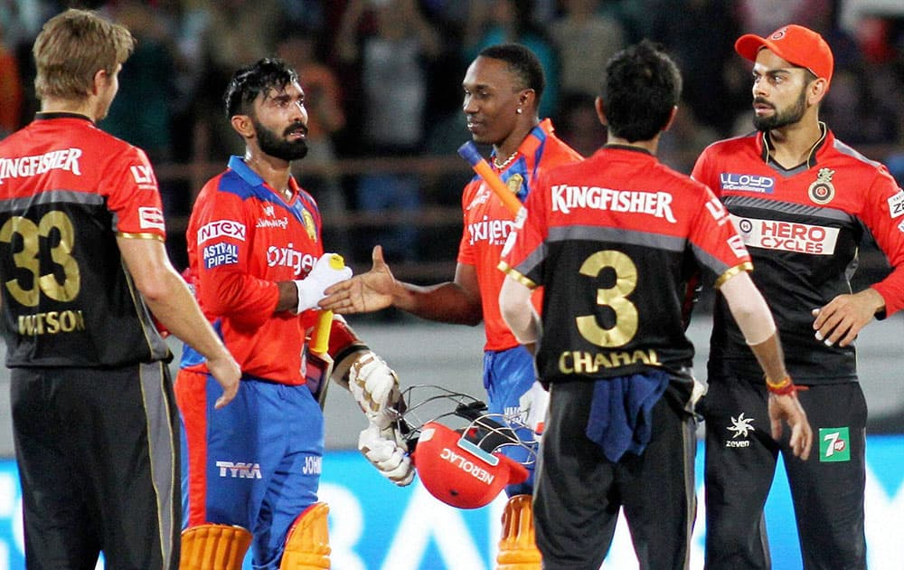 Gujarat Lions players Dinesh Karthik and Dwayne Bravo after winning IPL match against Royal Challengers Bangalore in Rajkot.