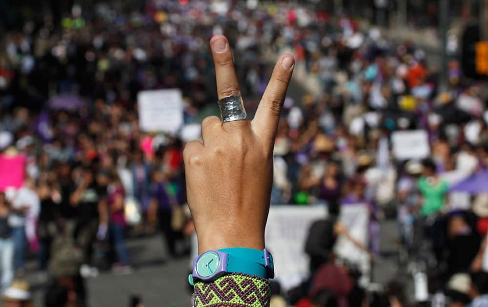 A female demonstrator flashes a victory sign as thousands protest against violence against women, in Mexico City.