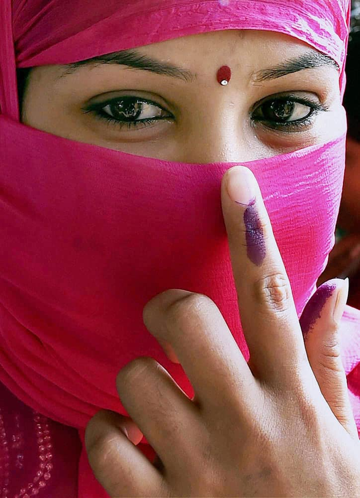 A woman shows her ink marked finger after casting vote during 4th phase of state assembly polls.