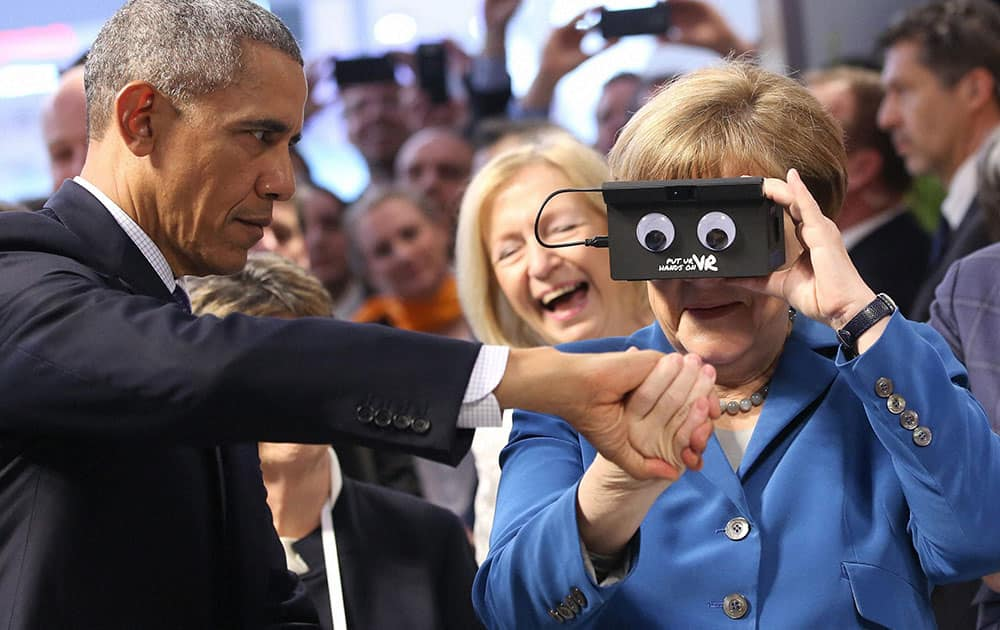 U.S. President Barack Obama, left, holds the hand of German Chancellor Angela Merkel as they test VR goggles when touring the Hannover Messe, the worlds largest industrial technology trade fair, in Hannover, northern Germany.