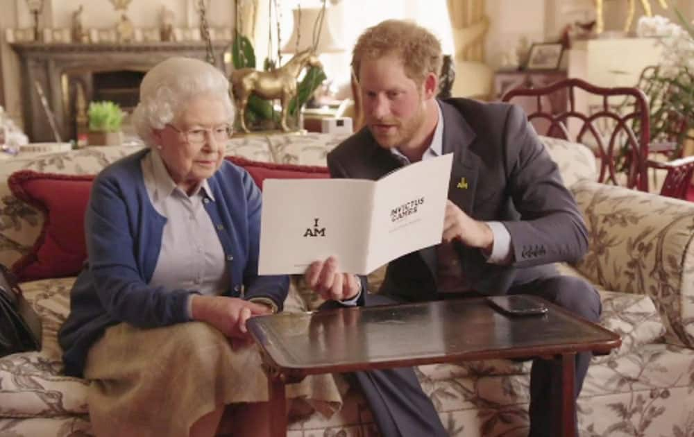 This image taken from a video released by Kensington Palace, London, on Friday April 29, shows Queen Elizabeth II sitting with her grandson, Prince Harry looking at an Invictus Games brochure. Prince Harry, released the video Friday promoting the upcoming Invictus Games for wounded veterans.