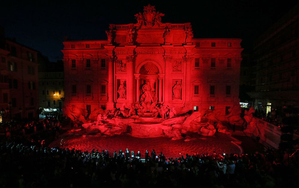 People gather to see the Trevi fountain illuminated red in memory of Christian Martyrs, in Rome.