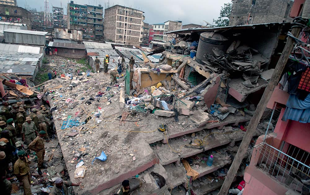 Kenyan police officers and Kenyan National Youth Servicemen search the site of a building collapse in Nairobi, Kenya.
