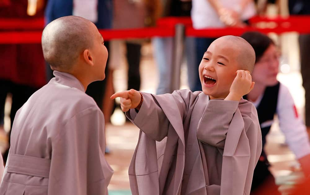 Two boys smiles after having their heads shaved during a service to celebrate Buddha's upcoming 2,560th birthday on May 14, at the Jogye Temple in Seoul, South Korea.