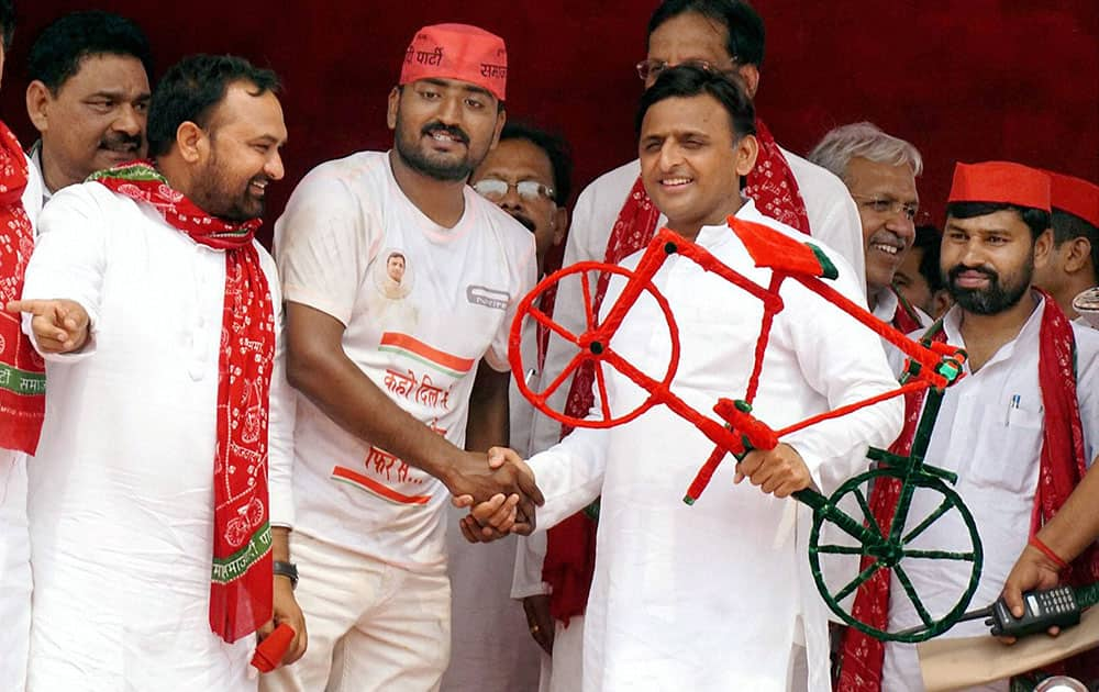 UP Chief Minister Akhilesh Yadav is presented a model of Samajwadi Party symbol cycle by supporters during a public meeting in Ballia.