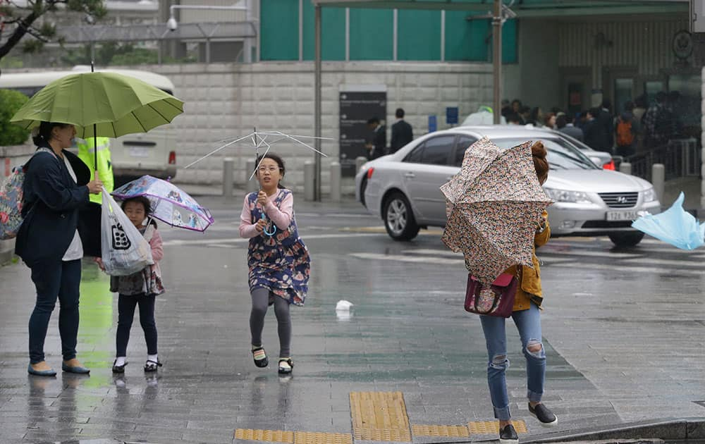 Passers-by try to manage their umbrellas in rain and strong wind in downtown Seoul, South Korea.