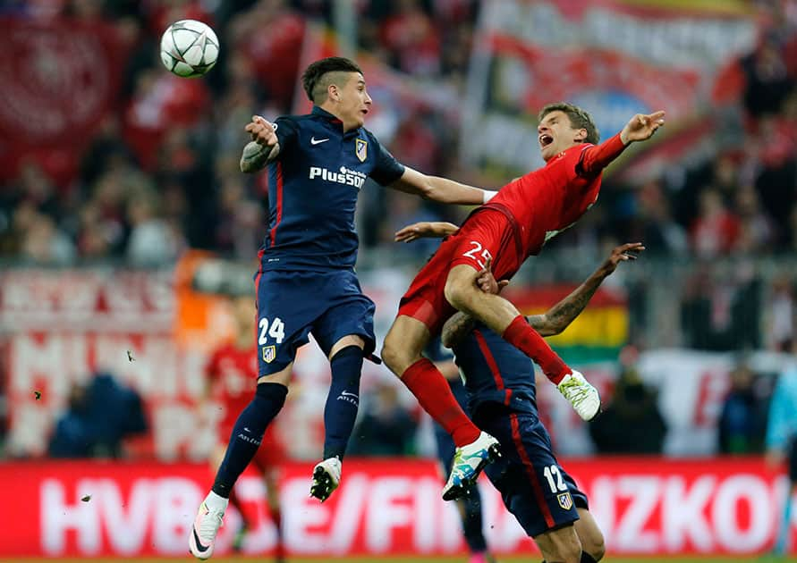 Atletico's Jose Maria Gimenez, left, and Bayern's Thomas Mueller go for a header during the Champions League second leg semifinal soccer match between Bayern Munich and Atletico de Madrid in Munich, Germany.
