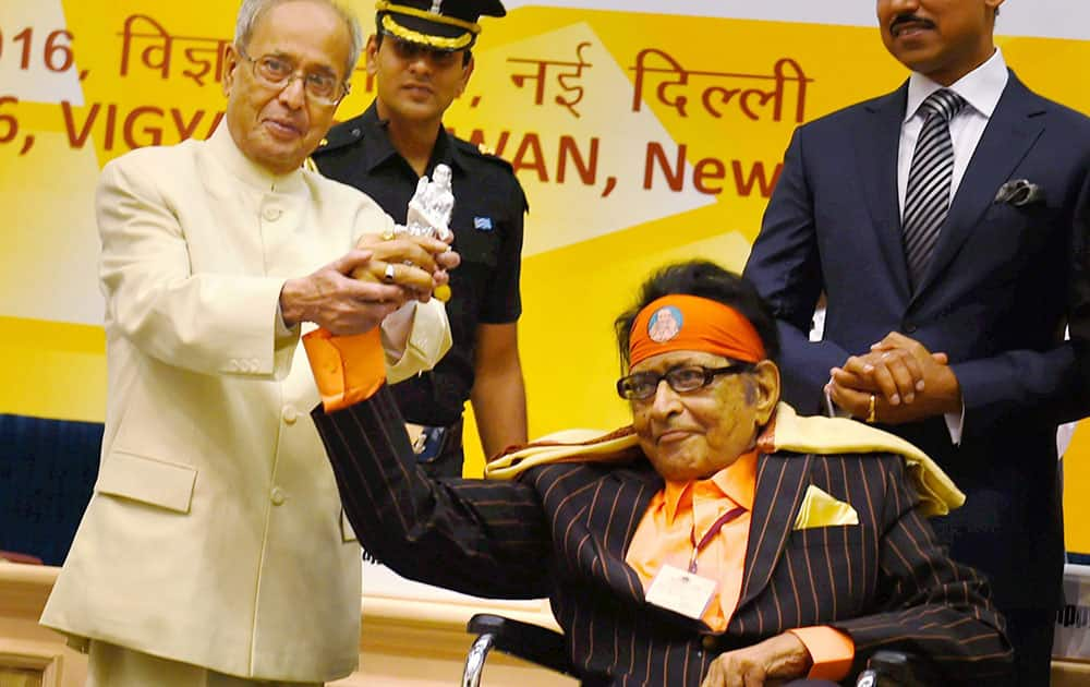 Veteran actor Manoj Kumar presenting a memento to President Pranab Mukherjee while receiving Dadasaheb Phalke Award from him at the 63rd National Film Awards 2015 function in New Delhi.