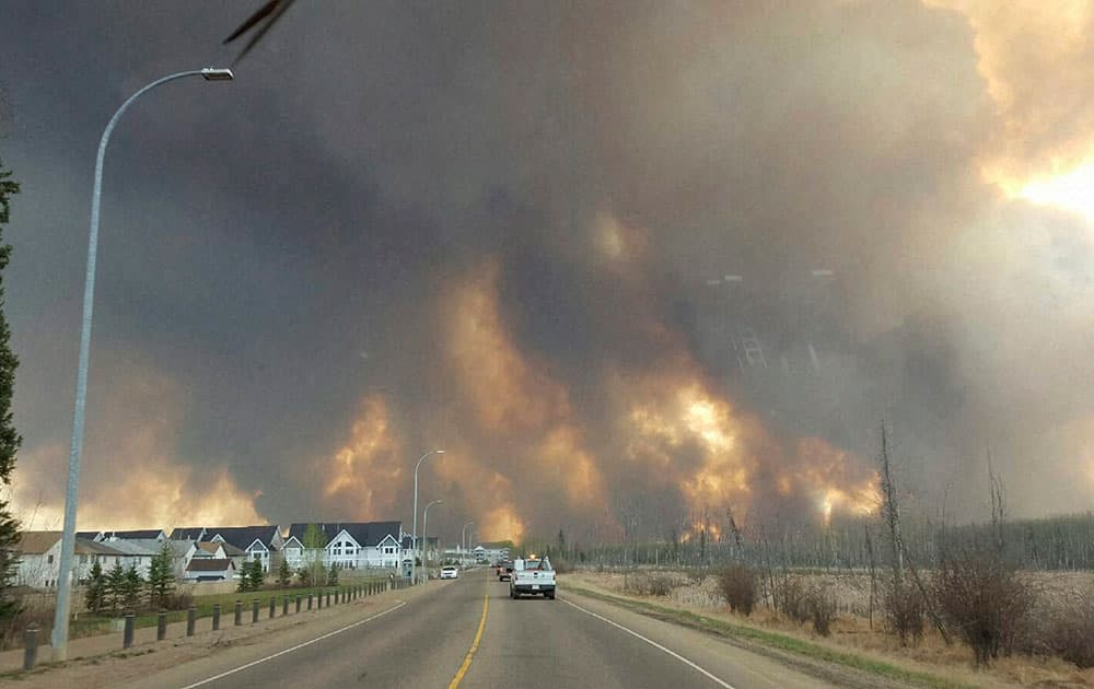 This photo taken through a car windshield shows smoke rising from a wildfire rages outside of Fort McMurray.