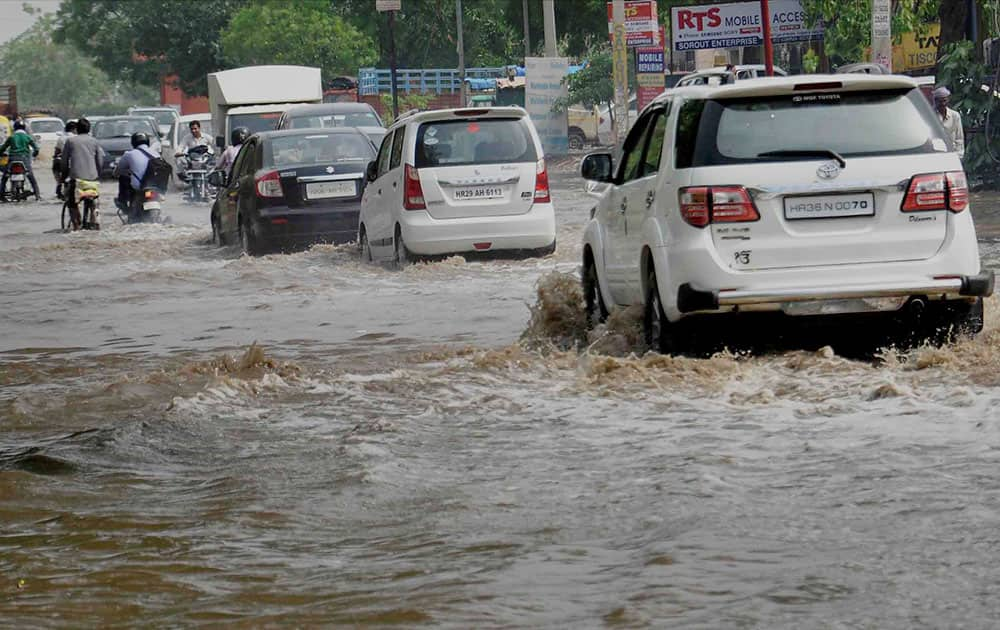 Vehicles move at a waterlogged road after heavy rains in Faridabad.