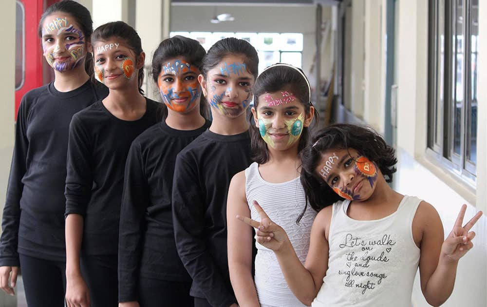 Girls paint faces expressing love for their mothers on the eve of Mothers Day in Gurgaon.