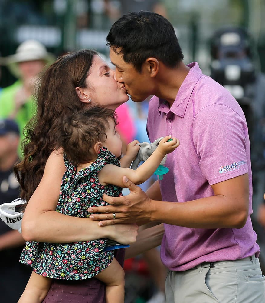 James Hahn, right, gets a kiss from his wife Stephanie and their daughter Kailee, center, watches after winning the Wells Fargo Championship golf tournament at Quail Hollow Club in Charlotte, N.C.
