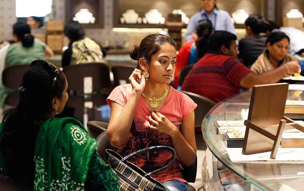 A woman tries on a gold earring at a jewelry shop in Ahmadabad. Monday marks the Hindu festival Akshay Tritiya, the birthday of Lord Parasurama who is the sixth incarnation of Lord Vishnu, which is considered auspicious for buying gold among other things.