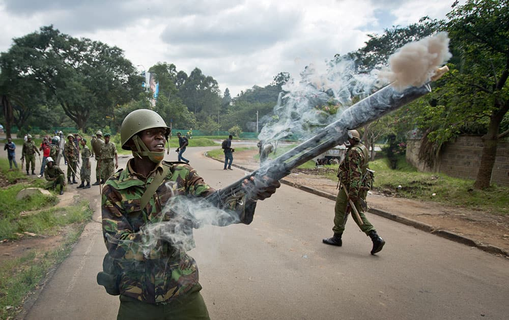 A riot policeman fires tear gas towards opposition supporters during a protest in downtown Nairobi, Kenya.