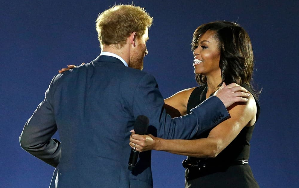 Britain's Prince Harry, left, greets first lady Michelle Obama on stage during the opening ceremony for the Invictus Games.