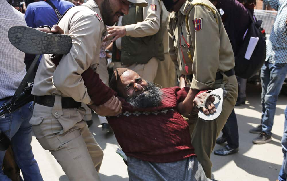 An activist of Jammu and Kashmir Handicapped Association is detained by police during a protest in Srinagar,Kashmir.