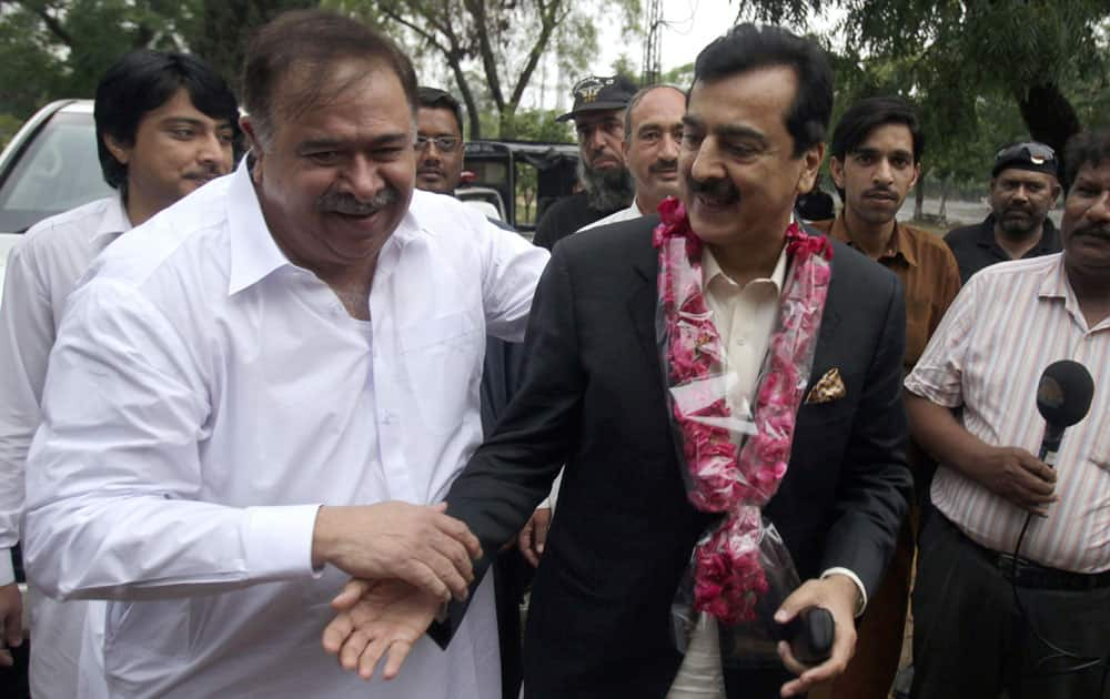 Pakistan's former Prime Minister Yusuf Raza Gilani, center, is greeted by supporters upon arrival at his residence in Islamabad, Pakistan.