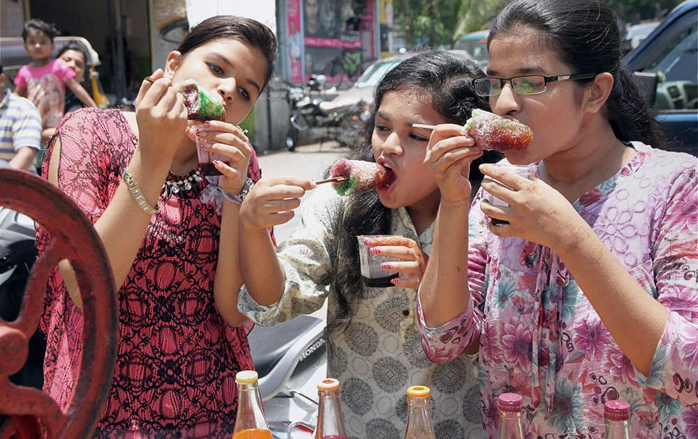 Girls enjoy ice-colas to beat the heat on a hot day in Thane, Mumbai.