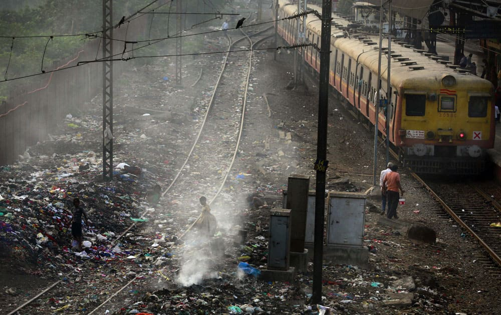 A local train moves past burning garbage at a local train station in Mumbai. The World Health Organization released new information from its Global Urban Ambient Air Pollution Database, that says 98 percent of residents in large cities of low- and middle-income countries are facing excessively high air pollution.