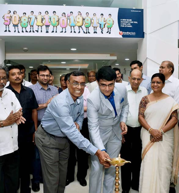 President of Cricket Association of Bengal and former captain of the Indian cricket team Sourav Ganguly and founder, MD and CEO, Bandhan Bank, Chandrashekhar Ghosh light the lamp at the inauguration of the 670th branch of the bank, in Kolkata.