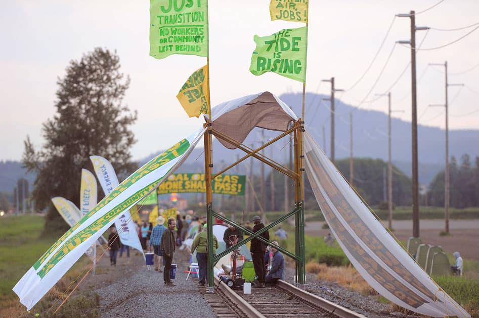 People congregate on the Burlington Northern Railroad tracks off Farm to Market Road in Skagit County in Burlington, Wash. Hundreds of people in kayaks and on foot are gathering at the site of two oil refineries in Washington state to call for action on climate change and a fair transition away from fossil fuels.