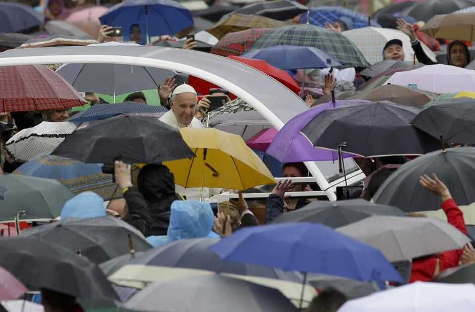Pope Francis greets people sheltering themselves from the rain under their umbrellas as he arrives for an audience for the Holy Year of Mercy, in St. Peter's Square, at the Vatican.