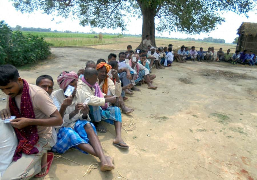 Voters wait in a queue to cast their votes during the sixth phase of panchayat elections at a polling booth at Ramgarhwa in East Champaran district of Bihar.