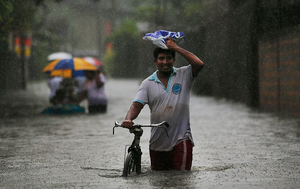An Sri Lankan man pushes his bike through a flooded area in Colombo.