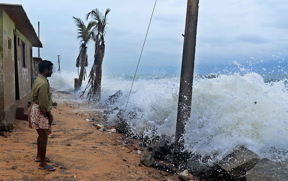 A man watches rough sea causing damage to houses in coastal areas in Thiruvananthapuram.