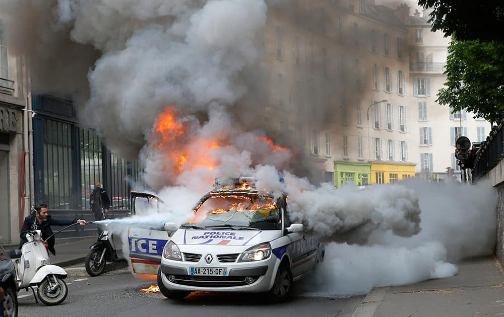 A man tries to pull off fire on a burning police car during clashes while police forces gather to denounce the almost daily violent clashes at protests against a labor reform in Paris.