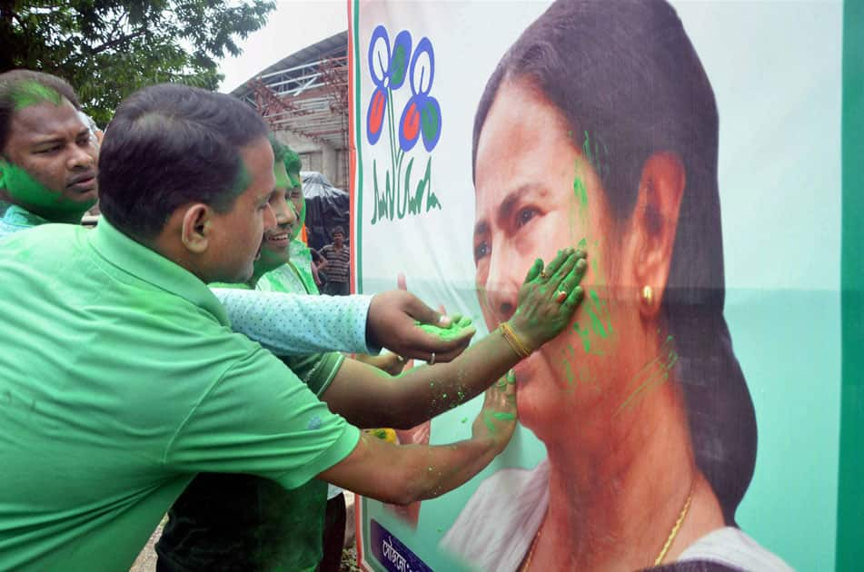 Trinamool Congress supporters smear color on a poster of party chief Mamata Banerjee as they celebrate their win in West Bengal assembly elections in Tripuras Agartala.