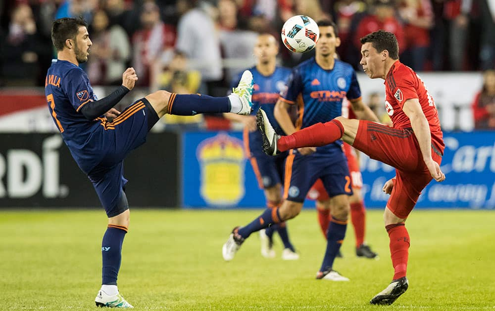 Toronto FC's Daniel Lovitz, right, battles for the ball with New York City FC's David Villa during the second half of an MLS soccer game against New York City FC, in Toronto.
