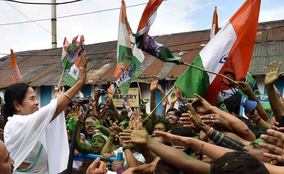 West Bengal CM Mamata Banerjee waves at supporters after her partys thumping win in West Bengal Assembly elections, in Kolkata.