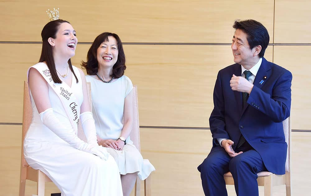U.S. Cherry Blossom Queen Reichel Bohn, left, chats with Japanese Prime Minister Shinzo Abe, right, as she pays a courtesy call at Abes official residence in Tokyo.