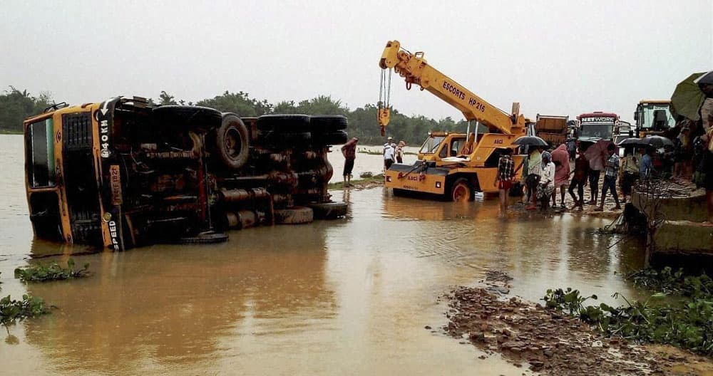 Road workers try to remove the accident vehicles on the National highway 44, due to the heavy rain and flooding in Solgoi in Krimganj district, Assam.