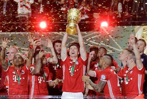 Bayern's Robert Lewandowski holds up the trophy after the German soccer cup final match between Borussia Dortmund and FC Bayern Munich in Berlin, Germany.