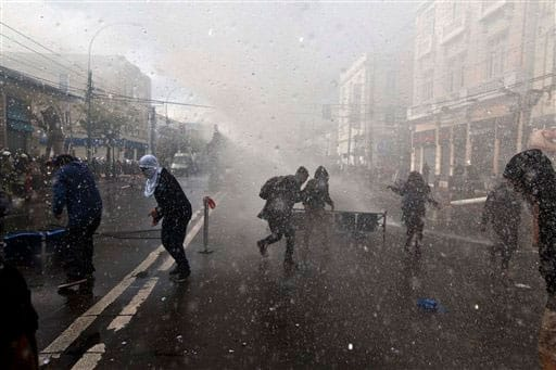 Protesters run from an approaching anti-riot vehicle blasting water, near Congress where President Michelle Bachelet was presenting the state-of-the-nation report, in Valparaiso, Chile.