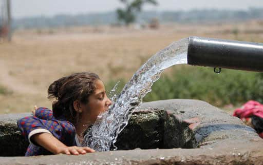 A girl drinks water from an irrigation tube, on a hot summer afternoon on the outskirts of Jammu, India.